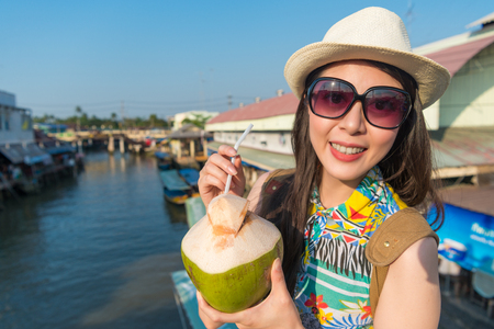 Asian female drinks the coconut drink to cool down her temperature under this fierce sunlight.