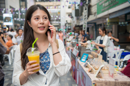 Asian woman holding a cup of mango juice and talking on her cell phone to share her trip with her family in hometown. Stock Photo