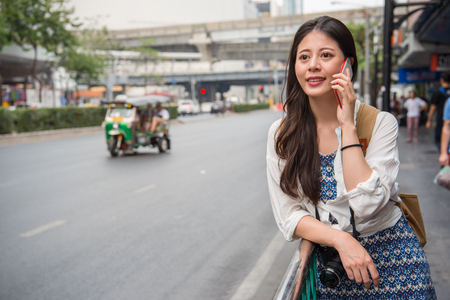 Asian female backpacker talking on the phone to connect her family and share her life with them. Stock Photo