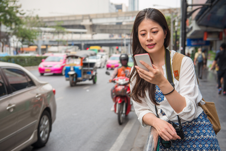 Asian female traveller taking a photo beside the road with her smart phone. She is wearing in casual.