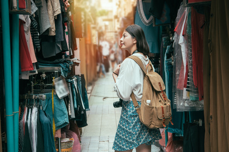 Asian female tourist shopping in the alley where is fulled of vendors and looking for the pretty clothes on the street market.