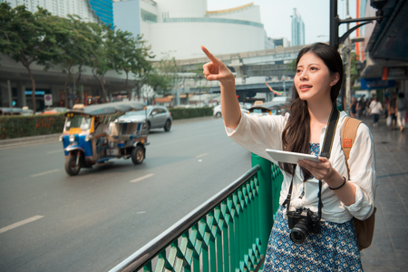 Asian woman stands beside the road and pointing to the front looking for the place shown on her pad.