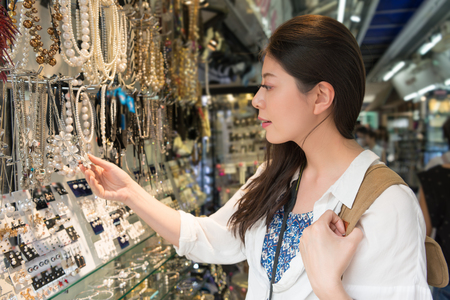 Asian woman shopping picking up the accessories at the vendor in the Siam square. This is a prosperous place in the Bangkok city. Stock Photo