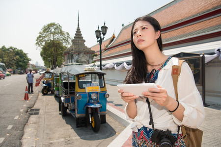 Asian woman is looking the correct way to go to her hotel since it is her first day in Thailand.