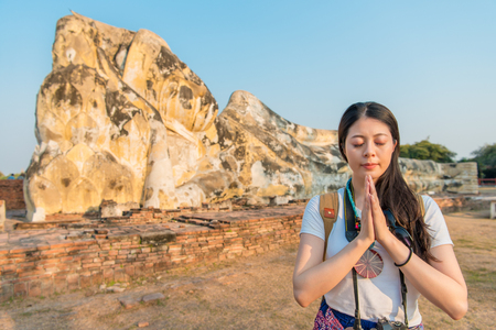 Female backpacker stands in front of the structure and take a picture looking at the camera.