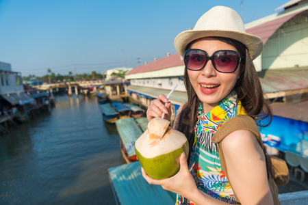 Asian female is so thirsty and sip the coconut drink she bought from the floating market. She uses a straw to drink it.