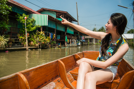 Young asian happy girl freedom raising her hands up and pointing to a traditional architectures on floating market in Bangkok, Thailand. Stok Fotoğraf