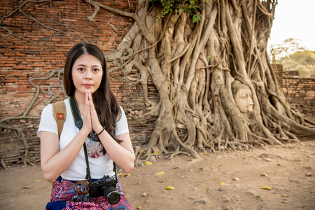 Asian woman put her hands together in front of her breast and kneeling down beside the road. She keeps her eye on the camera.
