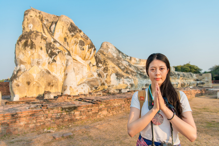 Asian female backpacker standing in front of the structure and take a photo with a brilliant smile and look at the camera. Stockfoto
