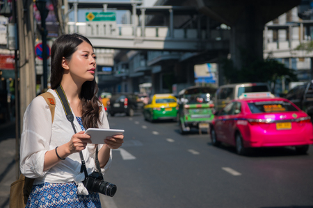 Asian female backpacker waiting for a cab aside the road in Thailand. She uses digital pad to search the road. Stock Photo
