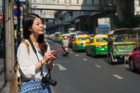 Young asian backpacker adult using smartphone or reading travel guide e book to find directions online during holidays. Stock Photo