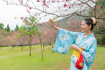 Asian woman standing under the cherry tree and raise up her hands to take a selfie with it. She would like to share with her fans on the social network. 版權商用圖片