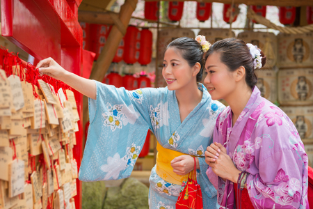 Two Asian woman hanging their wishes onto the wish walls. They expected to have goo luck in the future life. 版權商用圖片