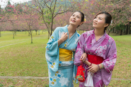 Two young Asian girls stand walking together enjoy the view of blossom cherry tree