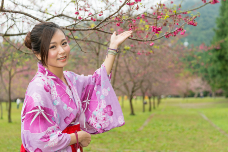 Asian woman standing under the cherry tree and raise up her hands to introduce the Sakura and take a photo with it. Reklamní fotografie