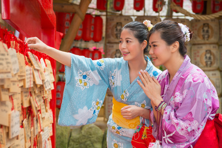 Two Asian woman hanging their wishes onto the wish walls. They expected to have goo luck in the future life. They are  devout and make wish from bottom of heart. 版權商用圖片