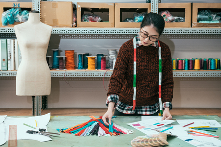 Asian female fashion designer choosing the appropriate zipper for the new designed clothes.
