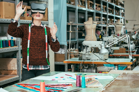 Asian woman wearing wearing VR headset to help her select the appropriate clothes material for the specific client. Banco de Imagens