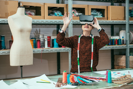 Asian modern intern wearing the virtual reality headset and grabbing something in the air.