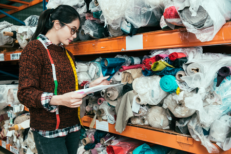 Asian woman manager searching the appropriate texture for the client. She is touching the fabric in the warehouse. Imagens