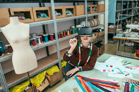 Asian woman wearing wearing VR headset to help her select the appropriate clothes material. Stock Photo