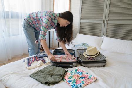 Seitenansicht der asiatischen Touristin, die ihren Koffer vorbereitet. Sie faltete alle Kleider schön und ordentlich zusammen.