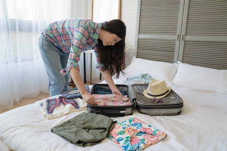 Side view of the Asian female tourist preparing her suitcase. She folded every clothes nice and neat.