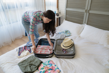 Asian modern female putting her clothes into the luggage. She is getting ready for her field trip in the coming future. 版權商用圖片 - 104440847