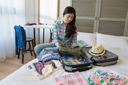 Asian woman folding and putting her clothes into the suitcase. She is preparing for her coming business trip.
