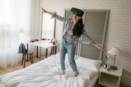 Asian childish woman wearing her VR device and open her arms as like she is a bird flying in the sky. Banco de Imagens