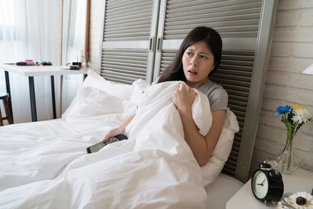 Asian woman lying in her bed and afraid to see the bloody scene showing on the television. Imagens - 104440856