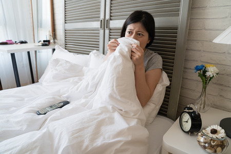Asian woman lying in her bed and do not dare to see the scary fiction woman. She cover her face with the blanket. Imagens - 104441039