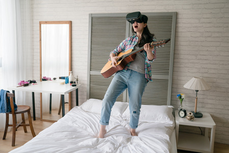 Asian woman wearing VR device headset playing the guitar video game with excitement and joyful. Banco de Imagens