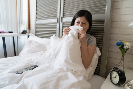 Asian woman feel disgusting to see the bloody scene in the movie and she covered her sight with the blanket. Stock Photo - 104441081