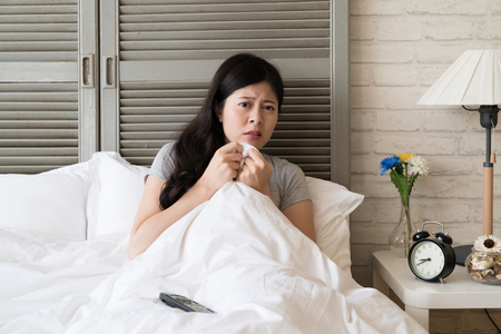Asian woman retreat into her bed while she is watching the climax of whole movie. She is so nervous and expect to see the ending.