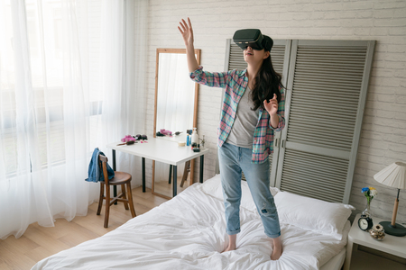 Asian female playing the VR device on her bed stretching her arms in the air as like she is grabbing and catching something the real world. 写真素材