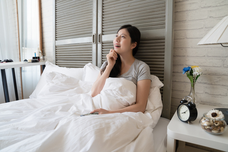 Asian woman thinking of the look of her boyfriend in the future. She lying in the bed and making day dream. Stock Photo