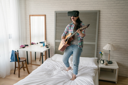 Asian female musician playing wooden guitar on her bed and wearing the VR. She used her VR device to Share her skill with her fans on social website.