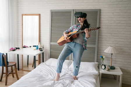 Female modern Asian woman leaning her body back and holding her wooden guitar and shouted and yelled as her room is a personal concert.