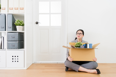 Asian woman sitting on the floor carrying her things with a box. She looks up to the ceiling and doesnt know where to go in next step. Stock Photo