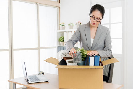 Asian woman packing and cleaning her office since she is going tho leave the company and resign.