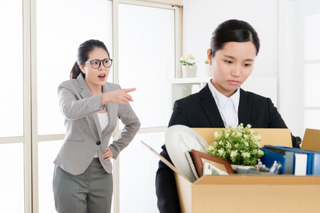 Asian employee scolded by the mean boss and leaving the office carrying her stuffs with helpless and low spirit.