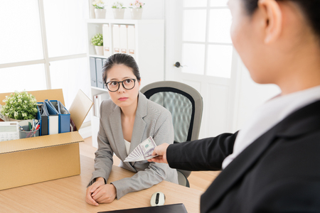 Una donna asiatica viene licenziata e il suo capo le ha dato una liquidazione. Non è disposta a partire. Archivio Fotografico - 104535523
