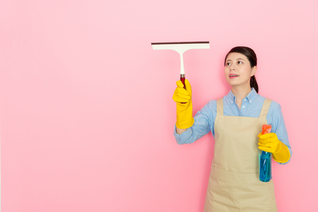 young girl housekeeper cleaning the window with tools on the isolated pink background.