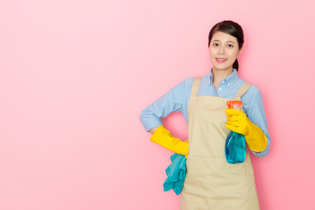 successful housewife holding a window cleaner liquid bottle face to the camera on isolated pink background