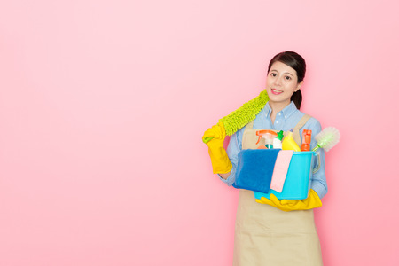 Asian woman holding a yellow feather stick standing at the pink background. She finally finished the work and has sense of successful. Standard-Bild