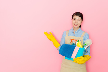 woman holding a box of cleaning tools face to camera isolated on pink background