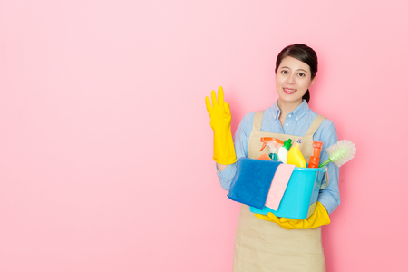 woman holding cleaning stuffs with toothy smile isolated on pink background