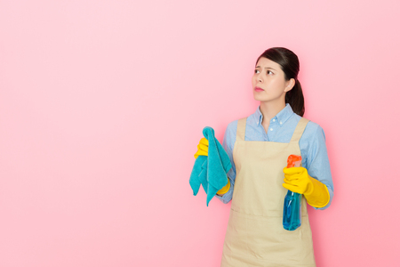 housekeeper holding a window clean bottle with difficult face expression on isolated pink background