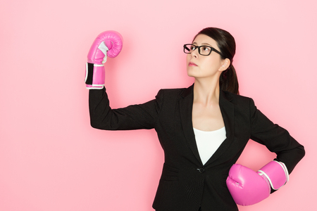business showing the powerful arm with wearing the boxing gloves isolated on pink background 写真素材
